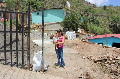 A young woman and her baby standing on the plot of land that has been prepared for the construction of her new home
