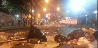 Opposition activists attempt to rebuild barricades in the wealthy neighbourhood of Chacao