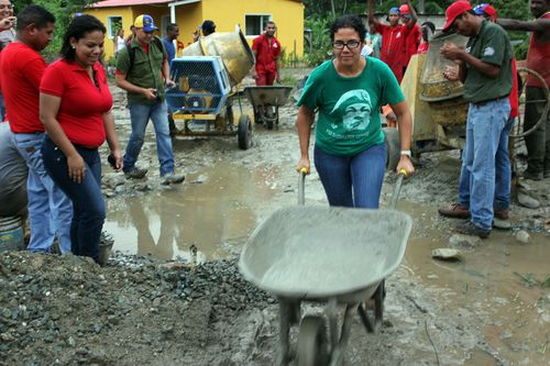 "Vice Minister of the Communal Economy, Ana Maldonado, lends a hand to the ""socialist Work Brigade"" labouring to build 51 new houses in the community."